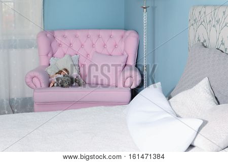 Blue bedroom and a pink armchair sweet home. Modern interior of room with armchair on blue wall background