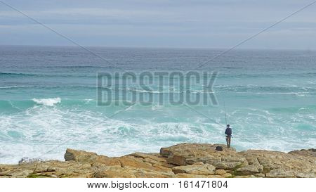 An angler on the Atlantic coast in the south of the Cape Peninsula, landscape in South Africa, endless expanse of the Atlantic ocean