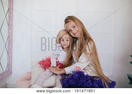 big sister hugging sad little sister. two girls in fluffy skirts
