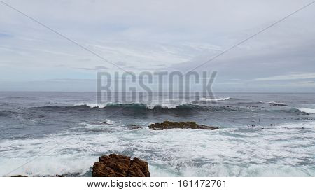 Surf bevor the south coast of Cape Peninsula in South Africa, rock on land and underwater,