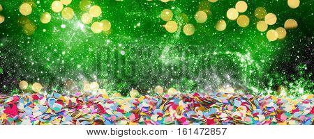 Colorful confetti with light spots in front of green background