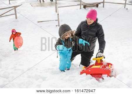Mother with son snow sledding and daughter with saucer sled in the background in snowy winter landscape having fun and enjoying family time. Family values parents love and happy childhood concept.