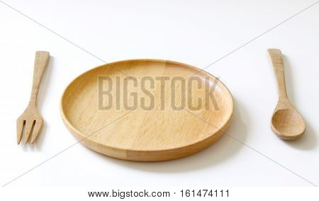 Wooden plate, spoon and fork on withe background