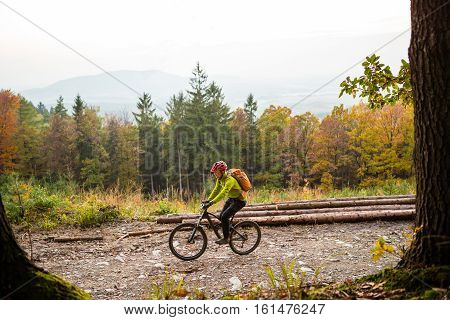 Mountain biker riding on bike in autumn or winter inspirational forest landscape. Man cycling MTB on dirty road in woods. Sport and active recreation fitness motivation and inspiration.