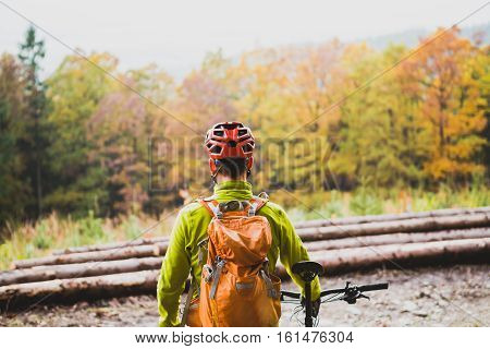 Mountain biker looking at inspiring mountain landscape celebrate and standing with bicycle. Man cycling MTB on dirty road in woods. Sport and active recreation fitness motivation and inspiration.