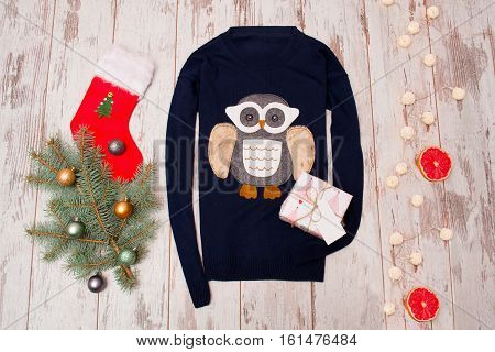 Blue sweater with an owl on a wooden background. Fur-tree branch with Christmas decorations stocking garland gift