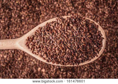 Healthy food diet. Closeup brown flax seeds linseed on wooden spoon