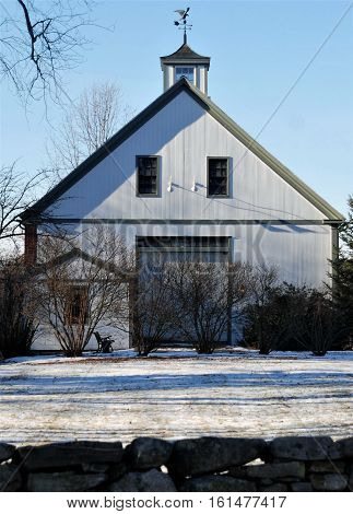 A 3 story white New England Barn in a Bright mid December day.  This photo is a companion photo of same barn photograped at dusk.