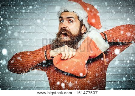 young handsome bearded santa claus surprised man in red sweater and new year hat holds decorative christmas or xmas stocking on white brick wall background under snow and snowflakes