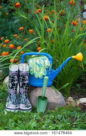 Gardening Tools. Rubber Boots Blue Watering Can Gloves And Shovel In Fiower Garden.