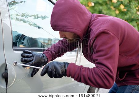Hooded Thief Trying To Open A Car Door Lock