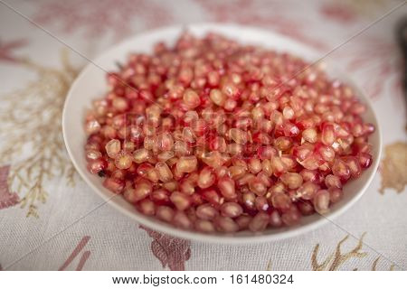Pomegranate Seeds in the white bowl at table