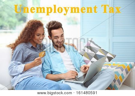 Tax concept. Young couple with credit card and laptop at home. Text UNEMPLOYMENT TAX on background