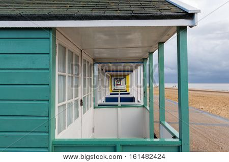 A close crop of beach huts showing a striking perspective at Southwold Pier in Suffolk