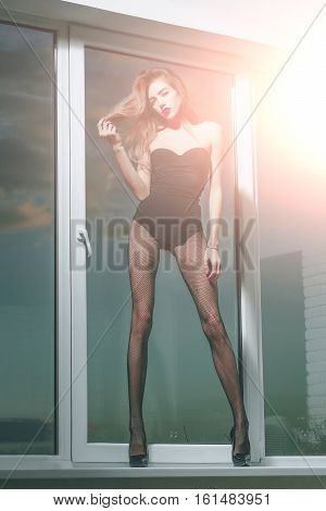 Pretty sexy girl young cute slim woman with long beautiful hair and legs in black fishnet tights fashionable shoes and lingerie stands at window on blue sky background