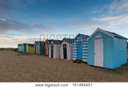 a view from the front of a line of colourful beach huts at Southwold Suffolk