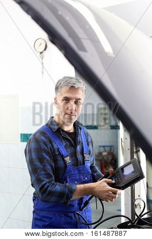 Car electrician. Electromechanics. Car repair, mechanic connected diagnostic device