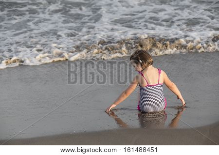 Girl sitting ang splashing through the waves on the seashore