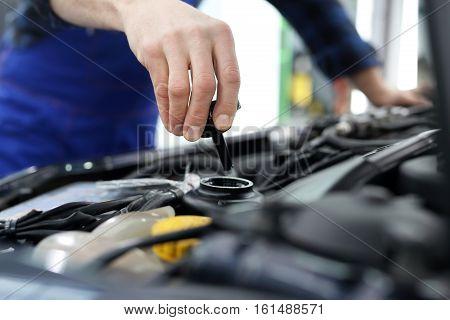 Steering fluid change. The mechanic fills the tank power steering fluid. Mechanic tightened the valve steering fluid reservoir. Car mechanic exchanges steering system fluid.