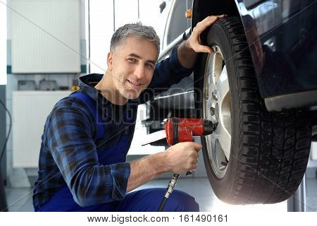 Tire service. Replacing the tires on the car. Mechanic adjusts the wheel alignment.