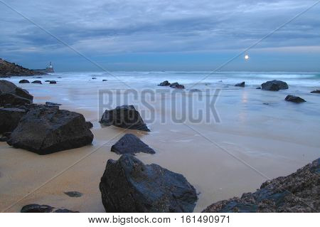 Moonrise on a rocky coastline with lighthouse in background.