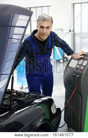 Service car air conditioning. Car air-conditioning, studded coolant. The mechanic fills and fumigation air conditioning in the car.
