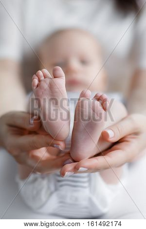 Happy mother tenderly holds his hands little feet of her newborn child,dressed in tee shirt and panties, white with black stripes,the woman's nails painted with white pearlescent paint,focus on feet baby
