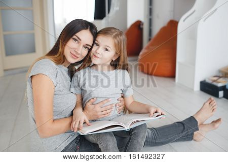 Young woman brunette with long straight hair,wearing a light gray t-shirt and grey jeans sitting on white floor with his daughter,a girl with blond long hair,wearing a light gray t-shirt,mother and daughter reading a book
