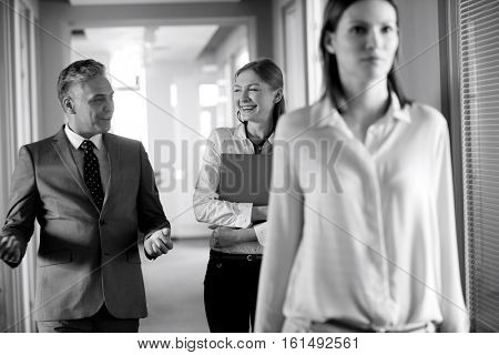 Businessman and businesswoman talking while walking in corridor with female colleague in foreground at office