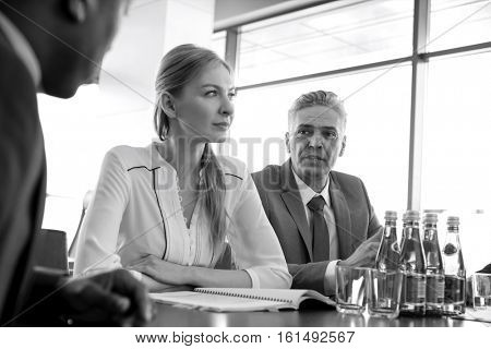 Mature businessman discussing with colleagues at table in board room