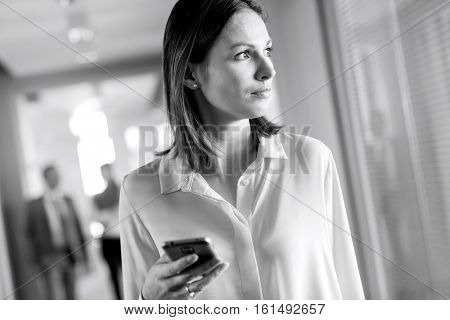 Young businesswoman holding smart phone while looking away at office