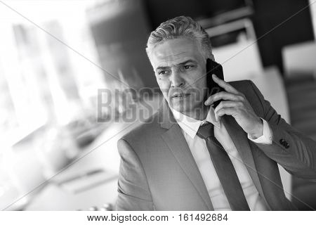 Mature businessman talking on mobile phone in conference room