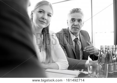 Mature businessman discussing with colleagues at conference table in office