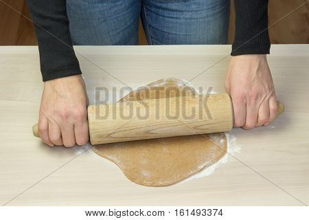 Rolling the dough by wooden rolling pin on the wooden board