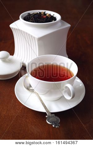 Flavored black tea in white porcelain dish on wooden table