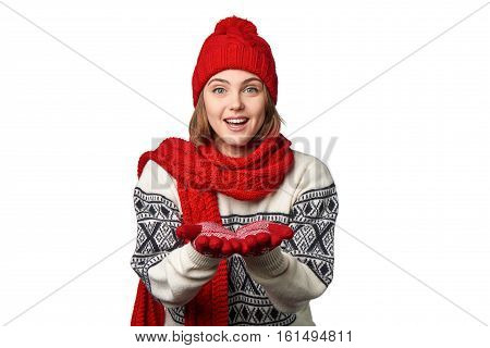 Happy woman wearing knitted warm scarf and hat holding opened palms in front of herself - copy space for product, looking at camera, over white background