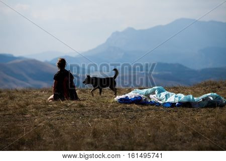 crumpled parachute on the background of mountains and tired glider with his dog