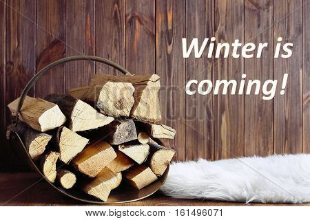 Basket with firewood and text WINTER IS COMING on wooden background.