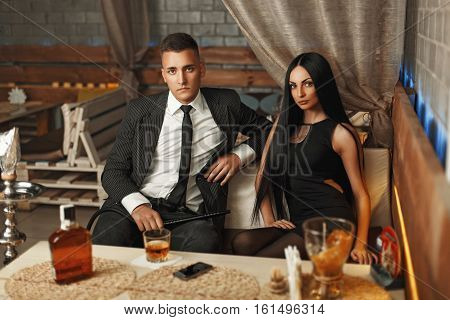 Handsome Man In An Elegant Suit With A Stylish Beautiful Woman Sitting On A Sofa In The Bar. Smoking