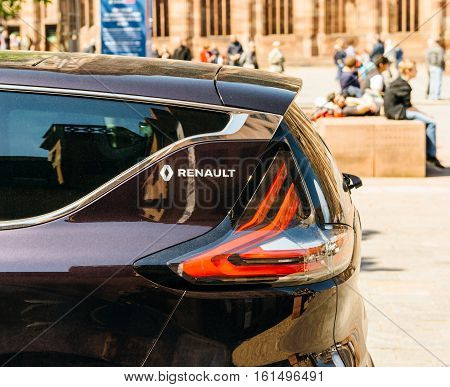 STRASBOURG FRANCE - MAY 4 2016: Renault logo on a luxury sedan RENAULT ESPACE INITIALE PARIS in urban environment with people standing on urban benches in the background. The Initiale logo is the flagship model and the most luxury one from Renault