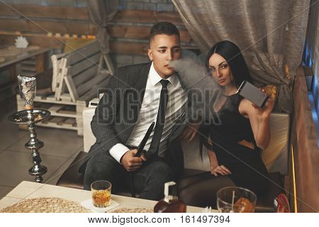 Elegant Stylish Couple Smoking Hookah And Makes Selfie On Smartphone