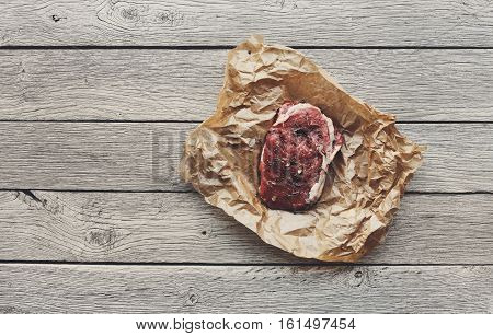 Raw beef steak in craft paper on dark wooden table background, top view. Fresh juicy meat food. Cooking ingredients, butcher's and grocery concept