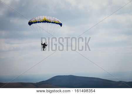 paraglider above the bay with mountains in sky