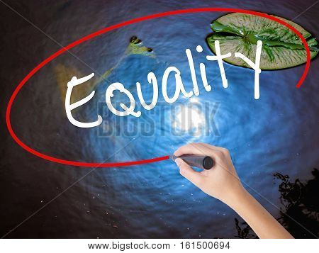 Woman Hand Writing Equality  With Marker Over Transparent Board