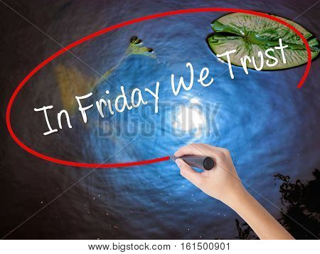 Woman Hand Writing In Friday We Trust  With Marker Over Transparent Board