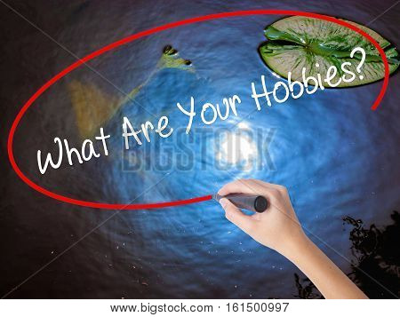 Woman Hand Writing What Are Your Hobbies? With Marker Over Transparent Board