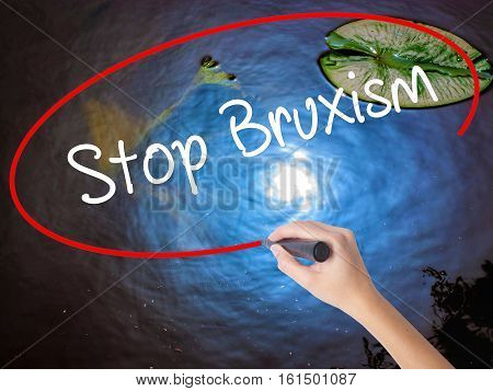 Woman Hand Writing Stop Bruxism With Marker Over Transparent Board