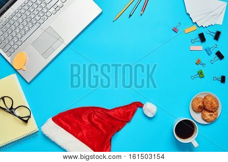 Top View of blue Office Table with cropped Laptop, clips, pencils, notebook with glasses and Christmas Theme Items Tree Santa Cap Notepad and coffe with cookie. business and Christmas theme