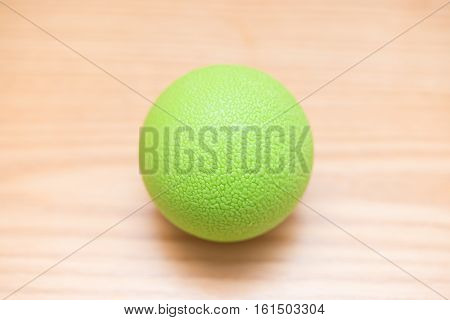 green small massage ball on a wood table