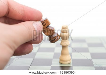 black chess player knocks down the white king with his Knight